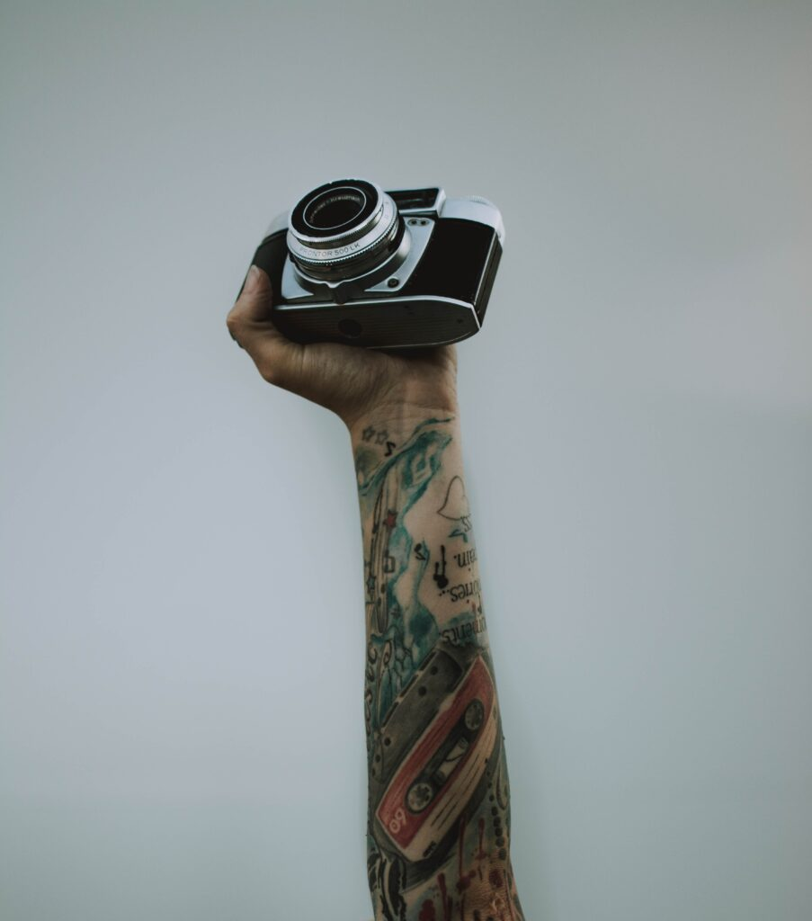Netflix photography documentaries you must watch. A hand holding a photographic camera.