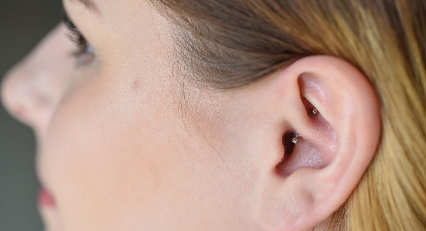 A guide for Daith Piercings. Woman with a daith piercing.