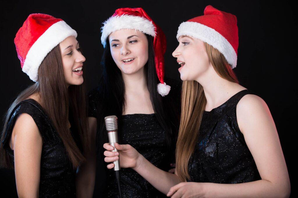 Die besten Weihnachtslieder zum Anhören. Drei Frauen singen Weihnachtslieder.