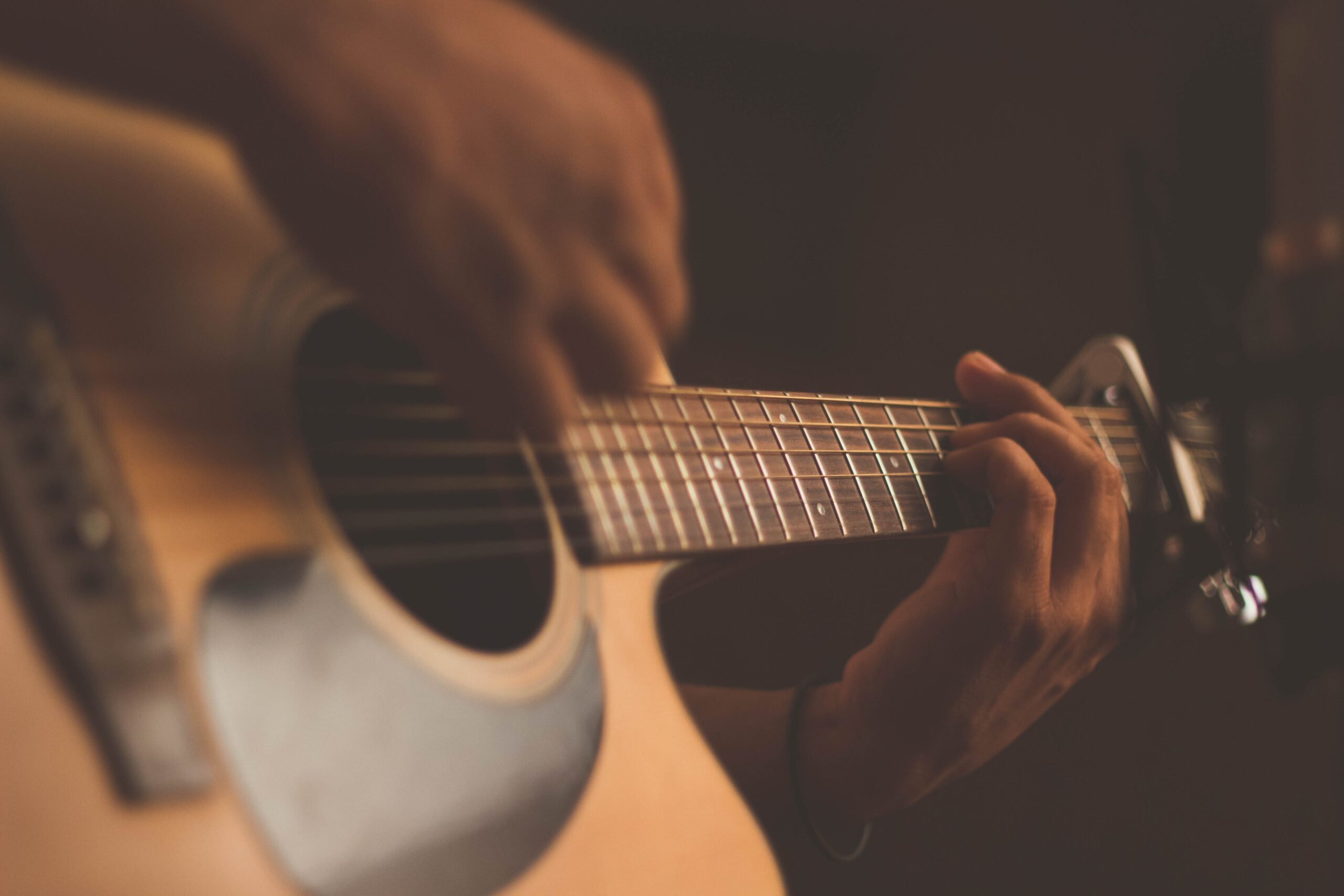 Who invented the guitar? The history of a great instrument. Man playing an acoustic guitar.