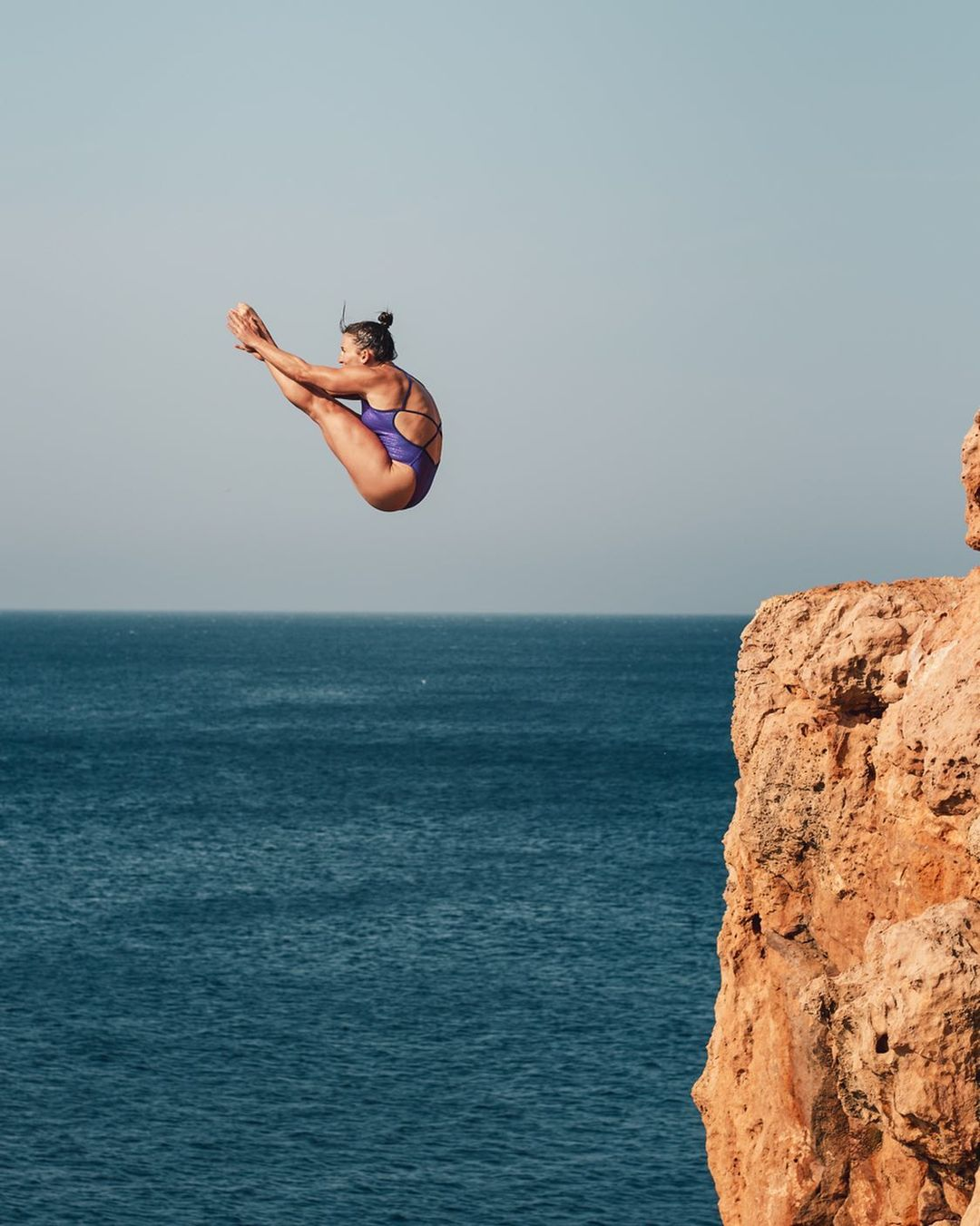A woman practicing cliff diving from a waterfall.