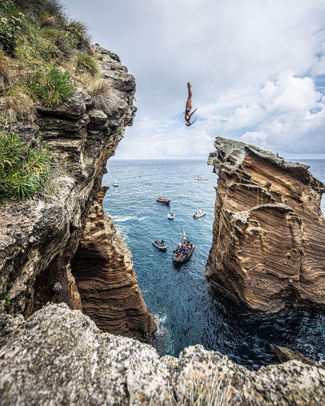 A woman doing acrobatics during cliff diving.