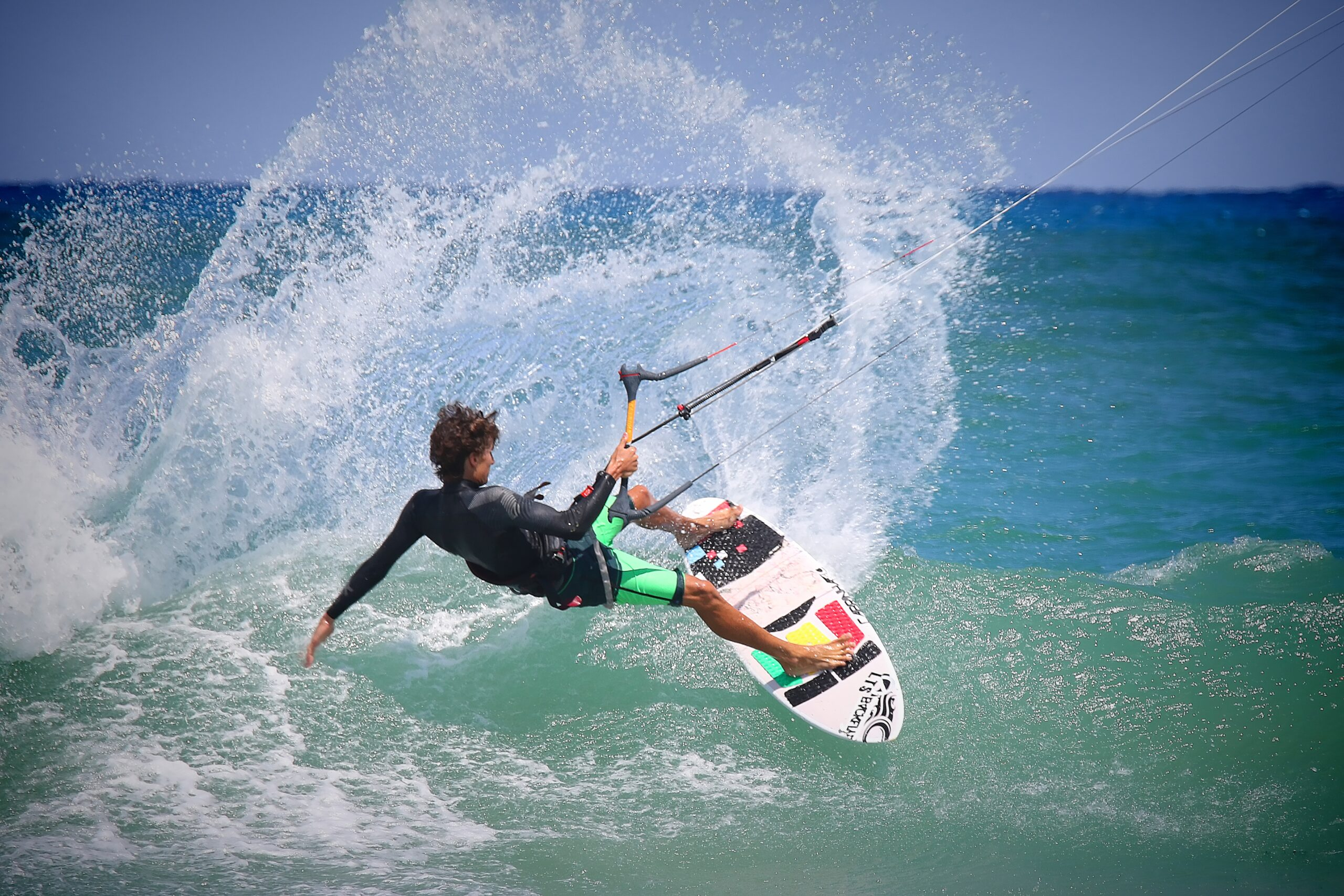 Young man practicing kitesurfing in the sea.