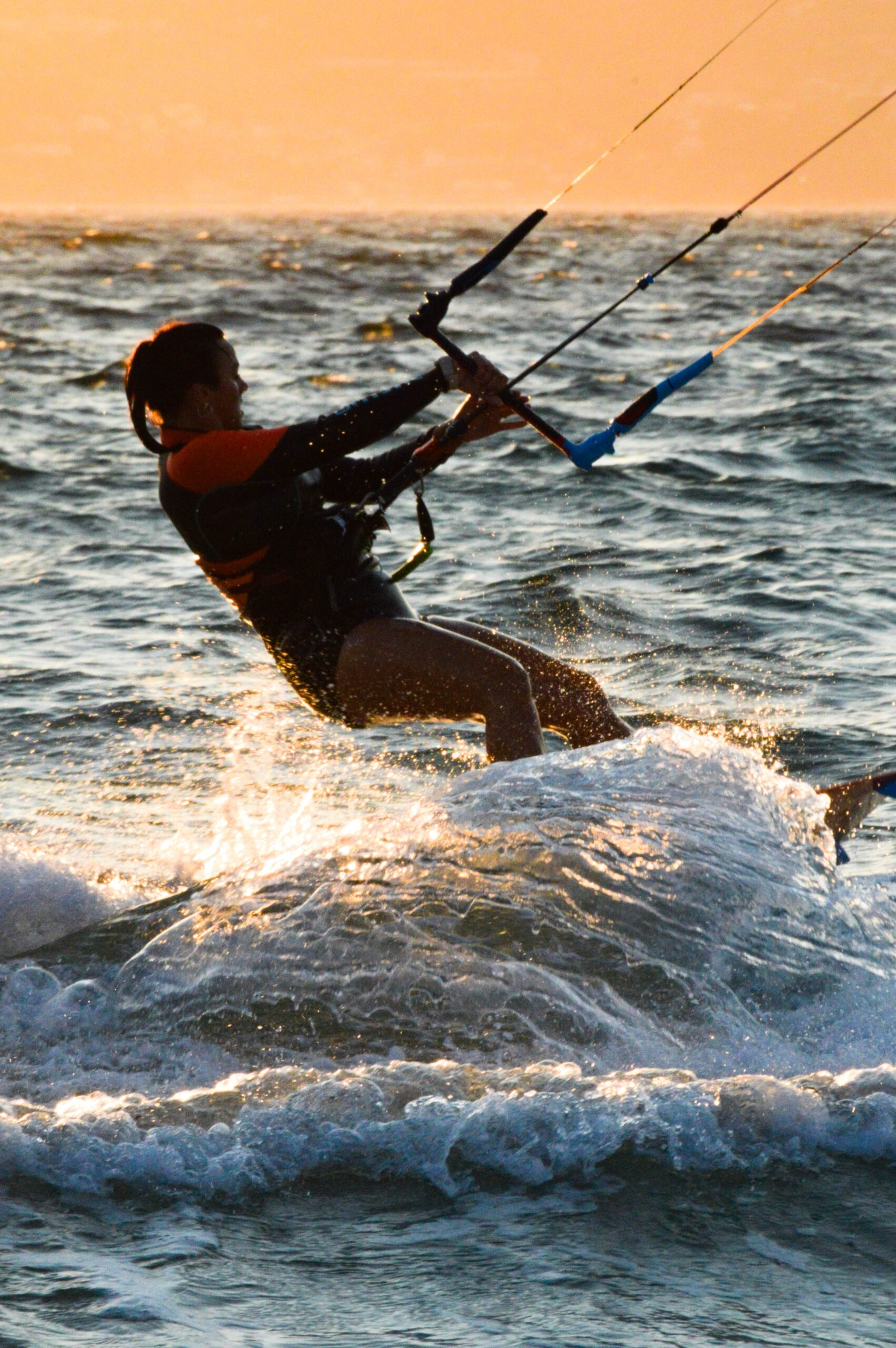 A woman practicing kitesurfing in the sea, at sunset.