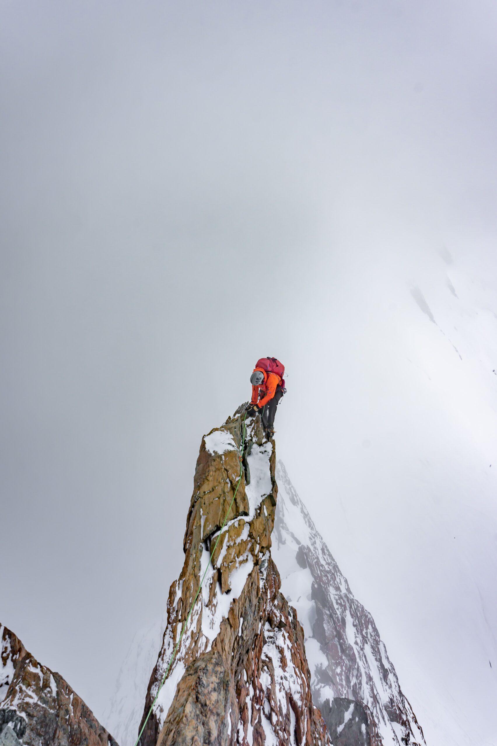Climbing Workout: a climber reaching the peak of a mountain.