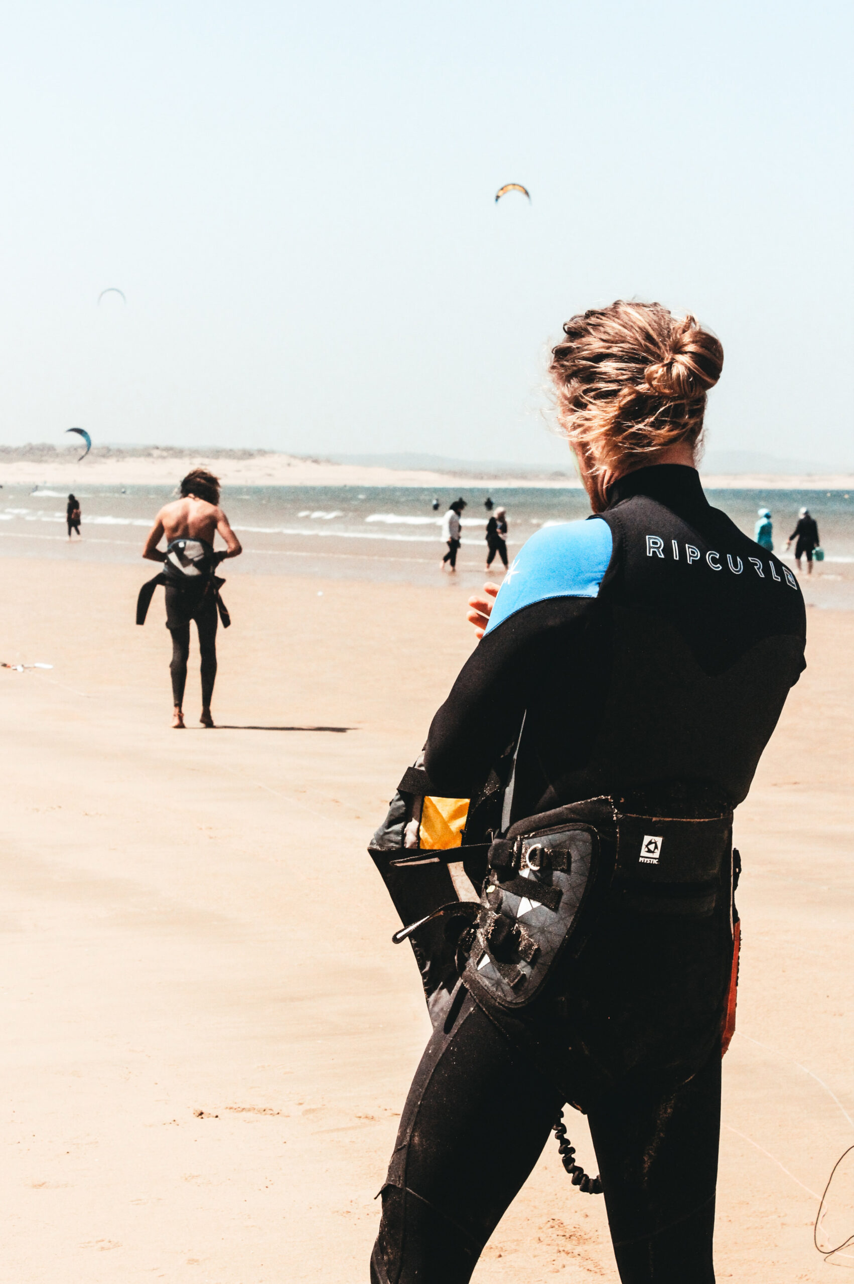 Man on a beach with the kitesurfing harness on.