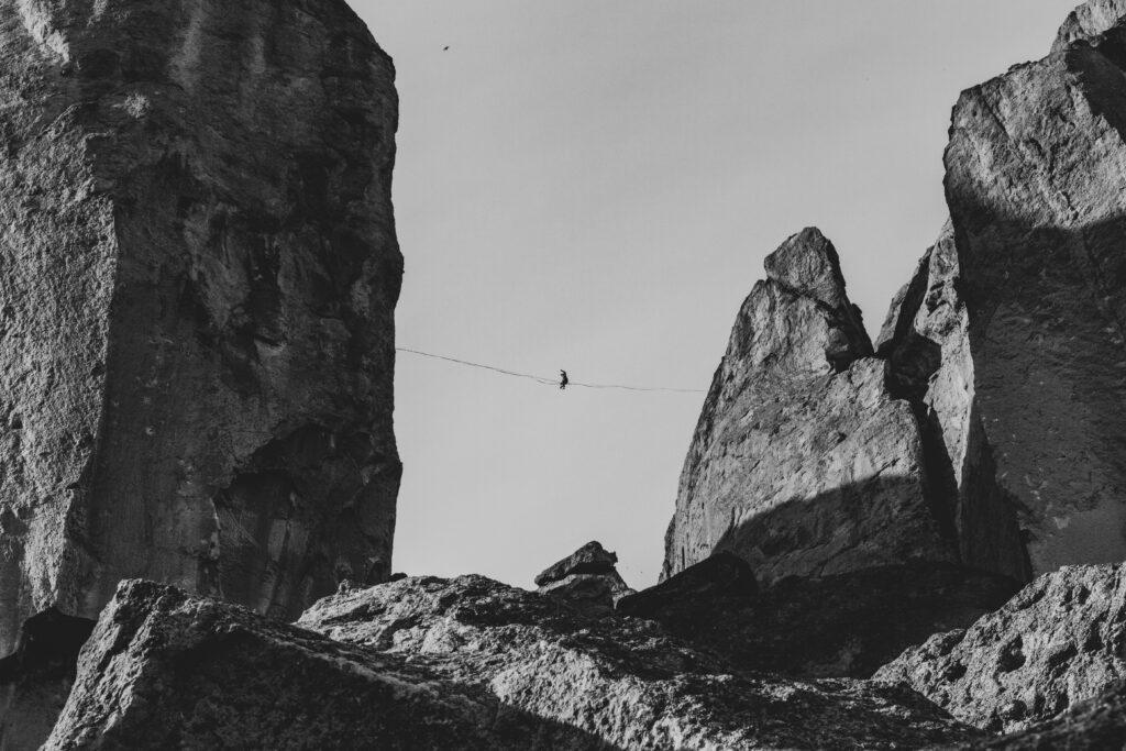 Highlining und Slacklining sind Balanciersportarten. Mann übt Highline zwischen zwei Gipfeln