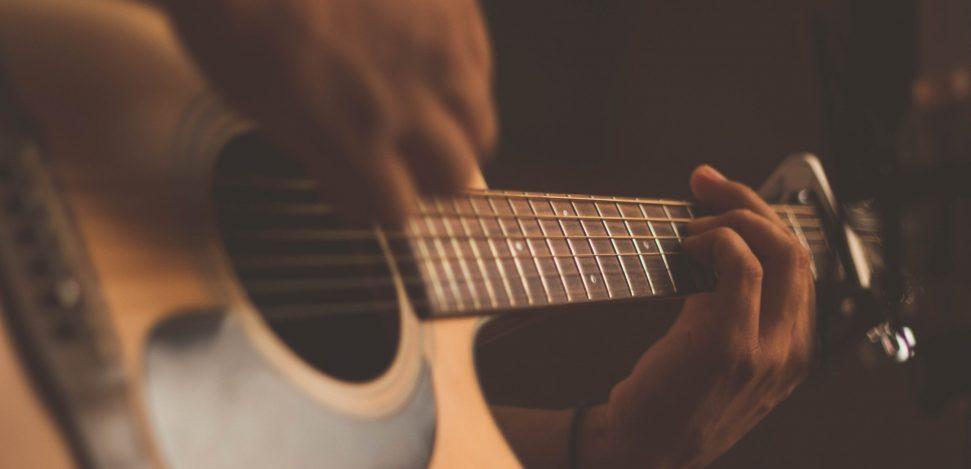 Wer hat die Gitarre erfunden? Die Geschichte eines großartigen Instruments. Ein Mann spielt eine akustische Gitarre.