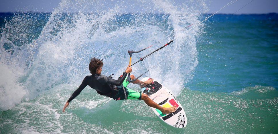 Junger Mann übt Kitesurfen im Meer.