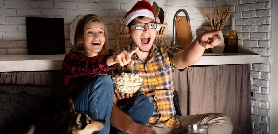Christmas movies you must watch! Young couple watching a Christmas movie.