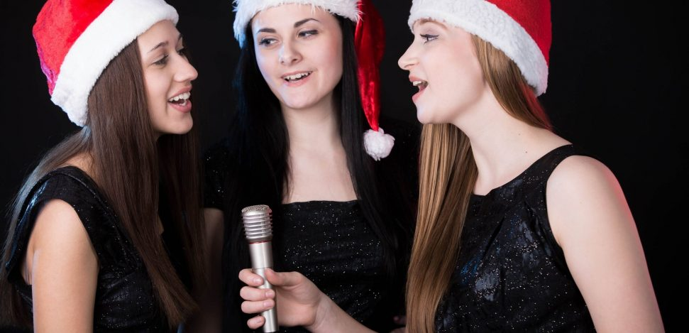 The best Christmas songs to listen to. Three women singing Christmas songs.